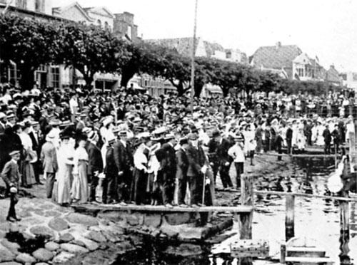 Travemünder Woche 1909 – Die große Hutparade. Mit Melonen und Strohhüten bedeckt werden die Segelyachten von einer große Menschenmenge erwartet.